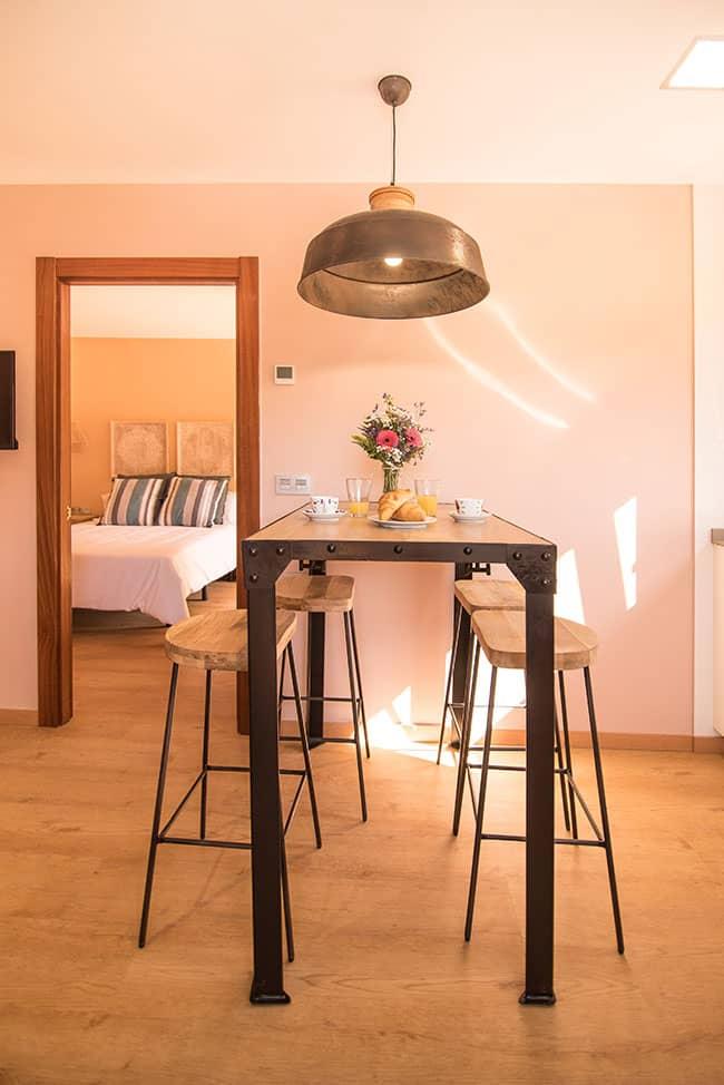 Mesa alta con cuatro taburetes en el salón comedor de apartamento del alojamiento agroturismo Zumintxaz