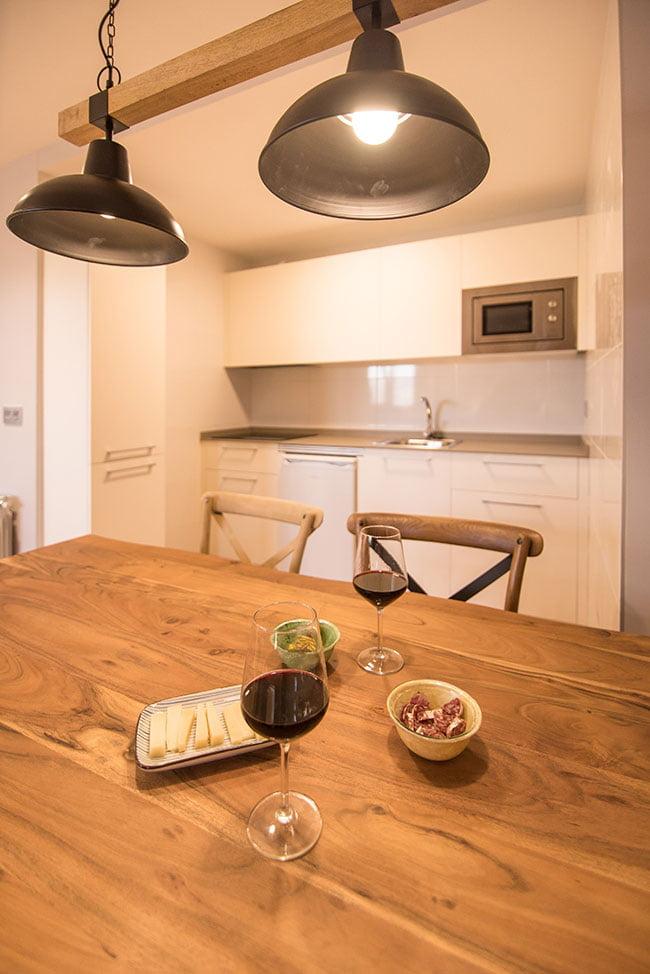 Detalle de la mesa del salón comedor, con copas de vino y un aperitivo, en uno de los apartamentos de agroturismo Zumintxaz